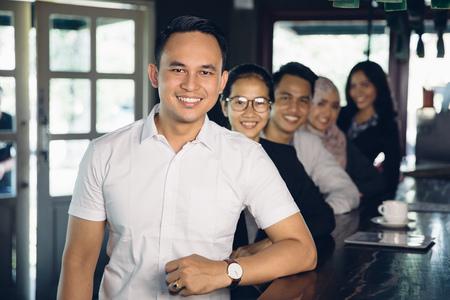 beau mec: portrait de leader d'affaires décontractée asiatique sur le premier plan de son équipe