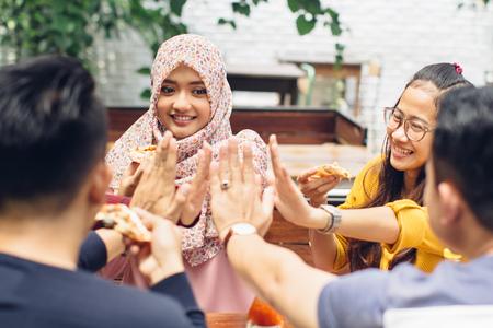 femmes muslim: portrait d'ami asiatique donnant high five � caf� tout en ayant un d�jeuner Banque d'images