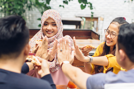 indonesian girl: portrait of asian friend giving high five at cafe while having a lunch
