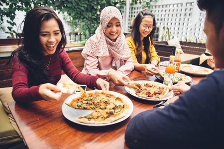 mujer sentada: Grupo de j�venes amigos disfruta de la comida en el exterior del restaurante