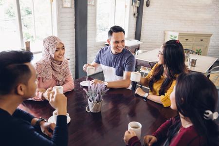Portret van vrolijke groep vrienden die een gesprek in het café
