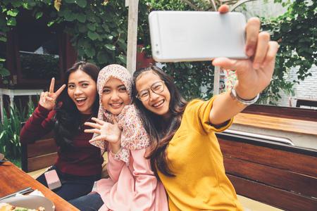 Portret van gelukkige jonge vriendin nemen selfie samen in cafe Stockfoto - 54706567