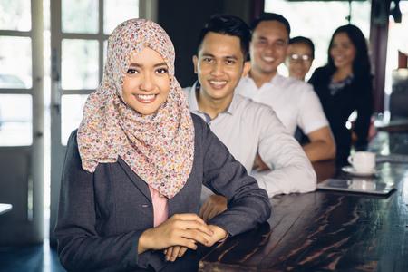 retrato de la hermosa empresaria asiática musulmana llevar bufanda de pie en frente de su equipo Foto de archivo
