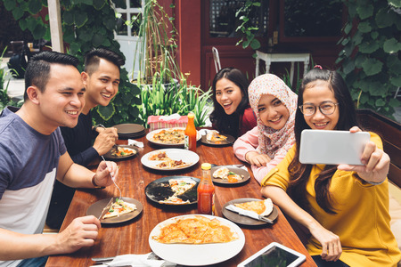 muslim: Group Of Friends Taking Selfie During Lunch Outdoors Stock Photo