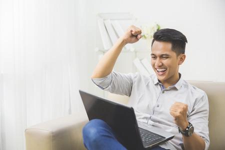joven excitado feliz con la computadora portátil en casa sentado en un sofá