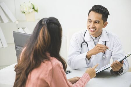 prescript: portrait of friendly Male Doctor explain something to the patient in a clinic