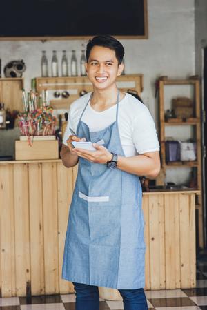 mandil: camarero masculino asiático feliz en el delantal para escribir y mirando a la cámara