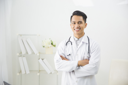 portrait of friendly Asian doctor man at his office smiling to camera