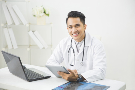 portret van gelukkig Aziatische arts met tablet in zijn kliniek Stockfoto