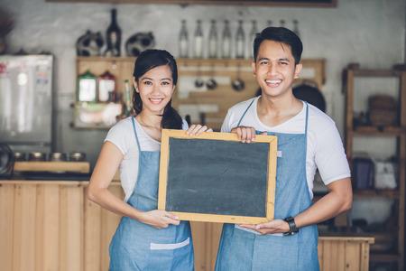 retrato de dos socios de negocios de jóvenes abrir su tienda de café. de pie con la muestra de la pizarra en blanco