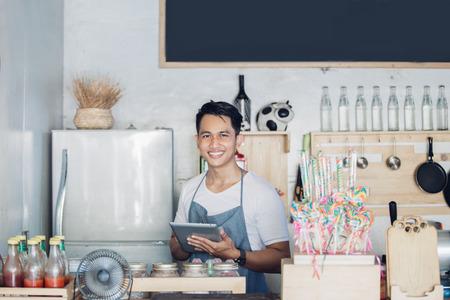 portret van de kleine ondernemer bij zijn coffeeshop met behulp van tablet pc Stockfoto