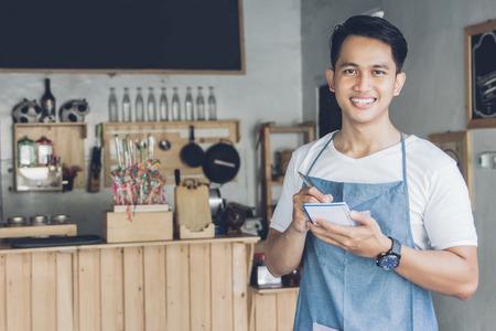 Gelukkige Aziatische mannelijke ober in schort schrijven orde en kijken naar de camera Stockfoto