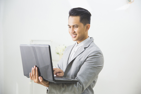 adult indonesia: Business man with a laptop over white background Stock Photo