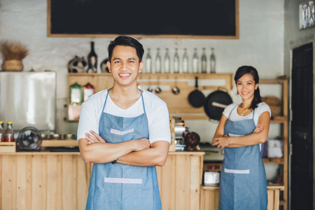 Successful small business owner standing with crossed arms with partner at the background Stock Photo