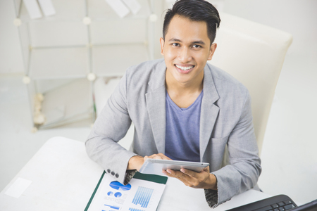 tab: portrait of handsome asian businessman using tablet pc at his office Stock Photo