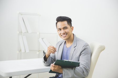 success man: Portrait of asian businessman working on his paperwork in the office