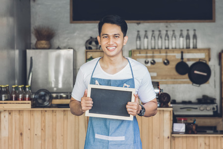 enterprising: portrait of confident young asian male cafe owner standing with blank board Stock Photo