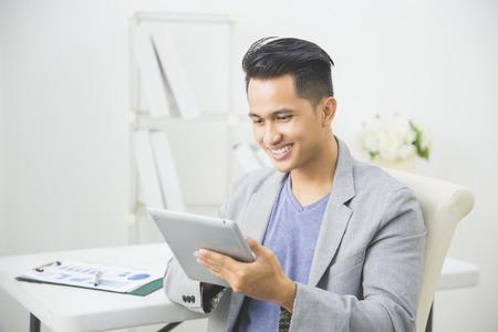 portrait d'homme d'affaires beau asiatique en utilisant la tablette pc à son bureau