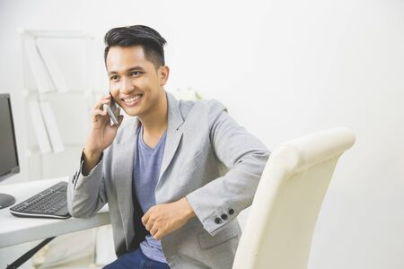 adult indonesia: Portrait of asian young businessman talking to the phone