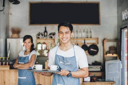 portret van jonge mannelijke ober serveert koffie op zijn eigen cafe Stockfoto