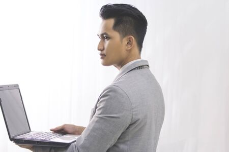 asian business man: Business man with a laptop over white background Stock Photo