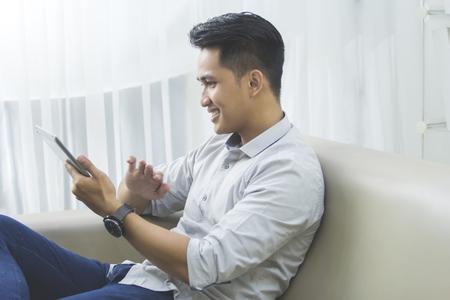 Portret van knappe Aziatische man met behulp van tablet pc thuis