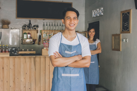Successful small business owner standing with crossed arms with partner at the background Banco de Imagens
