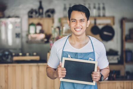 young asian: portrait of confident young asian male cafe owner standing with blank board Stock Photo