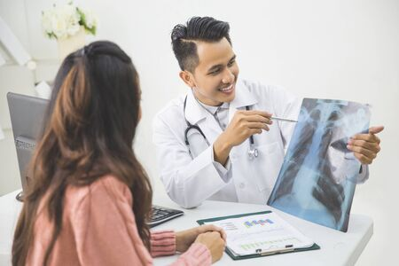 portrait of friendly Male Doctor explain something to the patient in a clinic