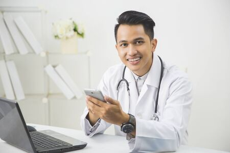 physician: portrait of happy asian doctor with mobile phone in his clinic