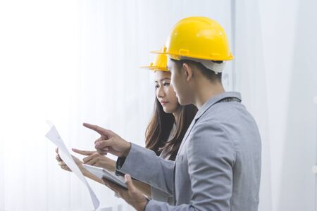 asian architect: business, partnership, architecture and people concept - smiling businessman and businesswoman with blueprint and helmets discussing