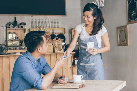 Glimlachende klanten betalen met contant geld in de coffeeshop Stockfoto