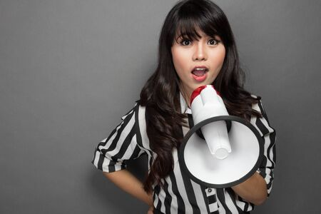 portrait of a young woman shouting with a megaphone against grey background