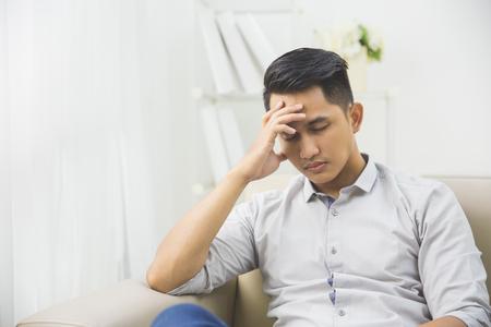 Portret młodego mężczyzny z problemami i stresem w domu siedzi na kanapie