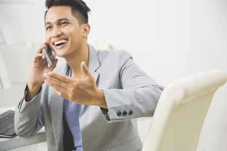 phone professional: Portrait of asian young businessman talking to the phone