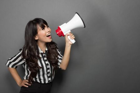 retrato de una mujer joven gritando con un megáfono contra el fondo gris Foto de archivo
