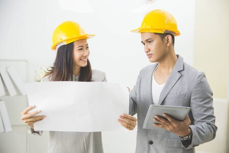 asian businesswoman: business, partnership, architecture and people concept - smiling businessman and businesswoman with blueprint and helmets discussing
