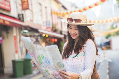 traveler girl searching right direction on map while exploring asian city Stockfoto