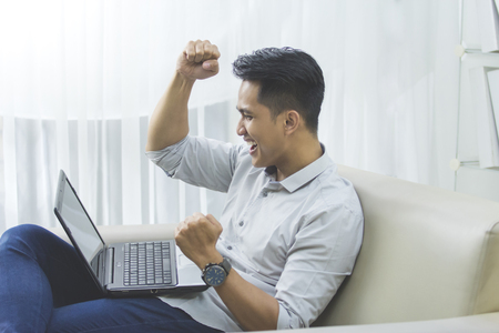 asian guy: happy excited young man with laptop at home sitting on a couch