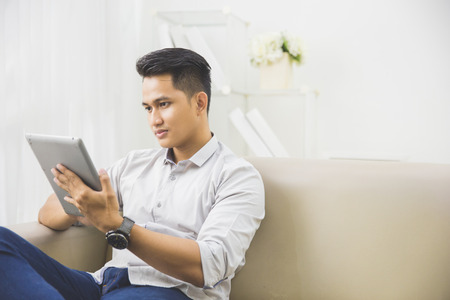using tablet: portrait of handsome asian man using tablet pc at home