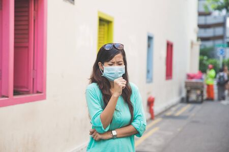 particulate: A woman wearing a face mask in the city coughing Stock Photo