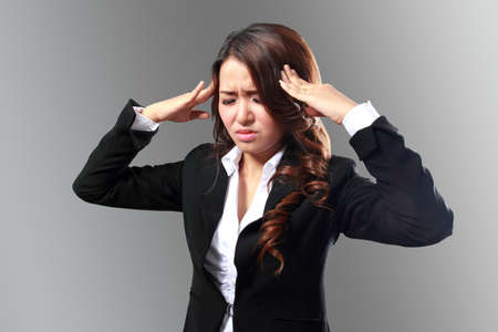 tormented: Young business woman with stressed at work Stock Photo