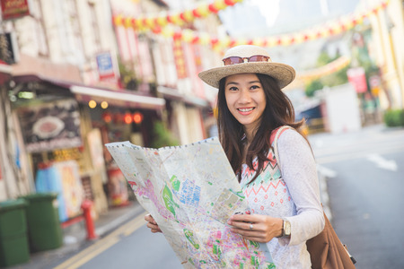 Gelukkig reizen vrouw kijken kaart en kijken naar de camera