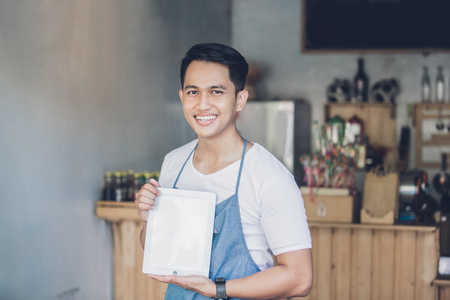 tablet: portrait of small business owner at his coffee shop using tablet pc