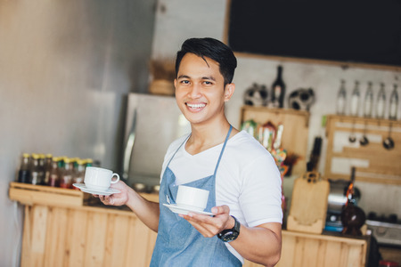 portrait of young male waiter serving coffe at his own cafe