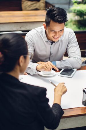 work together: portrait of businessman sitting in cafe discussing something with team