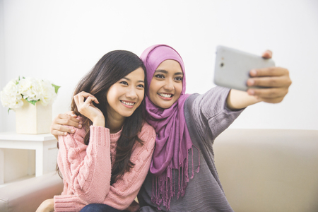 handphone: two happy young muslim woman take self portrait with handphone at home Stock Photo