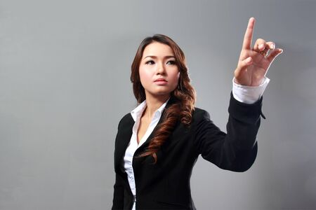 touch screen: Businesswoman pressing button or something. on gray background with copy space for your design. Stock Photo