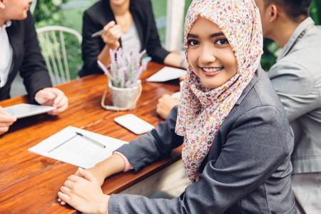 Atractiva empresaria asiática sonriendo a la cámara durante una reunión de negocios Foto de archivo - 57119314