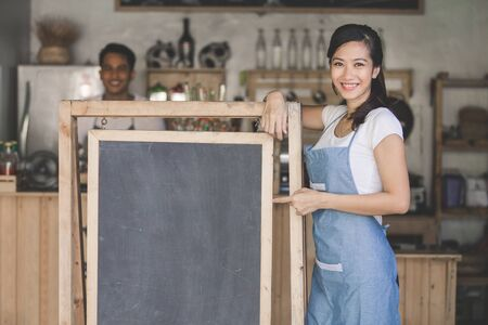 enterprising: portrait of attractive young asian female owner standing with blank board in her cafe